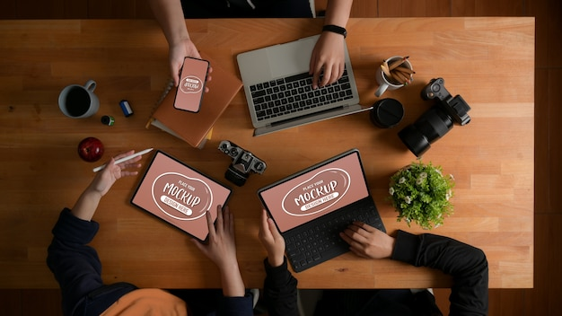 Vue de dessus du briefing de l'équipe de concepteurs sur leur projet avec maquette d'appareils