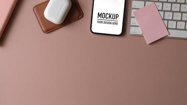Vue de dessus du bureau d'ordinateur avec maquette de smartphone