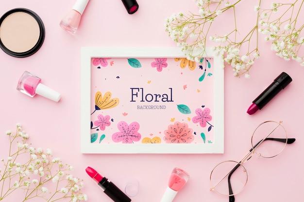 Vue de dessus du cadre avec des fleurs et des essentiels de maquillage
