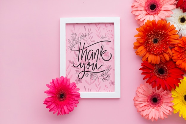 Vue de dessus du cadre et des fleurs avec un fond rose
