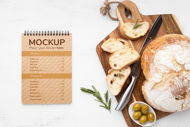 Vue de dessus du cahier avec du pain et des olives avec un couteau