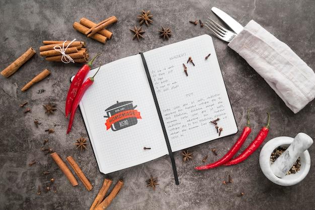 Vue de dessus du livre de recettes avec des couverts et des piments