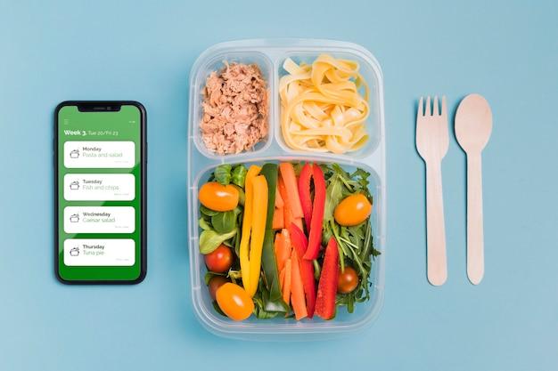 Vue de dessus du repas avec légumes et smartphone