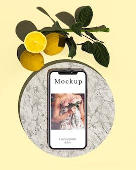 Vue de dessus du smartphone avec des feuilles et des citrons
