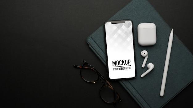 Vue de dessus du smartphone maquette sur ordinateur portable sur table noire avec accessoires