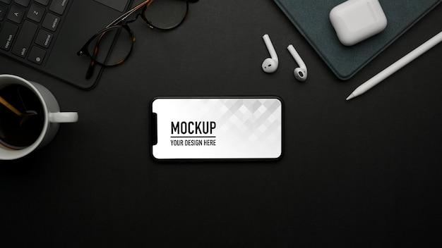Vue de dessus du smartphone maquette sur table noire avec accessoires fournitures et tasse à café