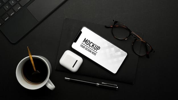 Vue de dessus du smartphone maquette sur table noire avec accessoires
