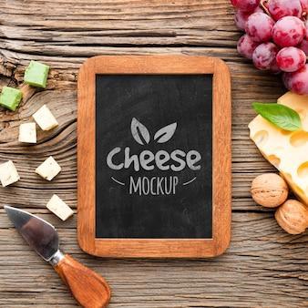 Vue de dessus du tableau noir avec assortiment de fromages et de raisins cultivés localement
