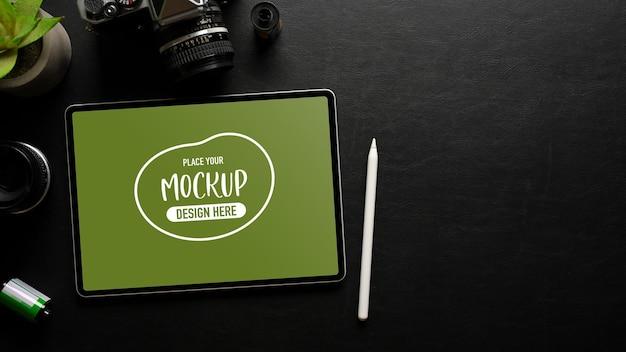 Vue de dessus de l'espace de travail créatif sombre avec appareil photo tablette numérique et espace de copie dans la salle de bureau à domicile