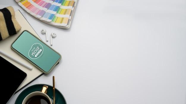 Vue de dessus de l'espace de travail avec maquette de smartphone, fournitures et espace de copie dans la salle de bureau à domicile