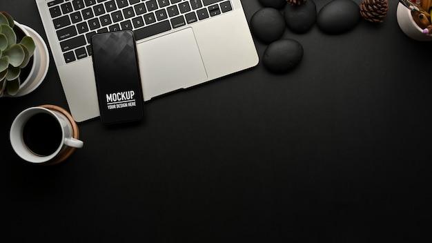 Vue de dessus de l'espace de travail avec maquette de smartphone sur ordinateur portable