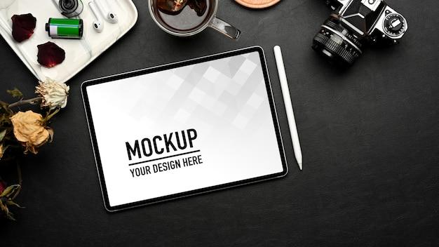 Vue de dessus de l'espace de travail avec maquette de tablette, fournitures et décorations sur table noire