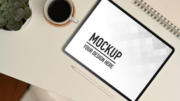 Vue de dessus de l'espace de travail avec maquette de tablette numérique, tasse à café et papeterie