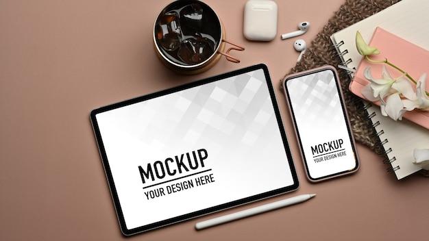 Vue de dessus de l'espace de travail avec maquette de tablette et smartphone et papeterie