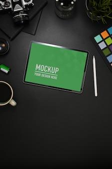 Vue de dessus de l'espace de travail avec maquette de tablette, stylet, appareil photo et fournitures