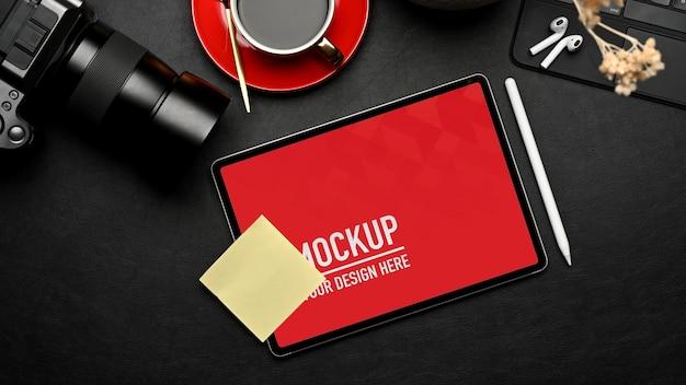 Vue de dessus de l'espace de travail avec maquette de tablette, tasse à café et fournitures sur table noire