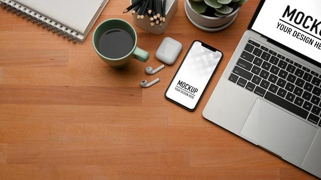 Vue de dessus de l'espace de travail avec ordinateur portable, maquette de smartphone
