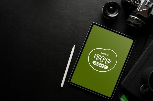 Vue de dessus de l'espace de travail sombre et plat créatif avec des fournitures pour appareil photo pour tablette numérique