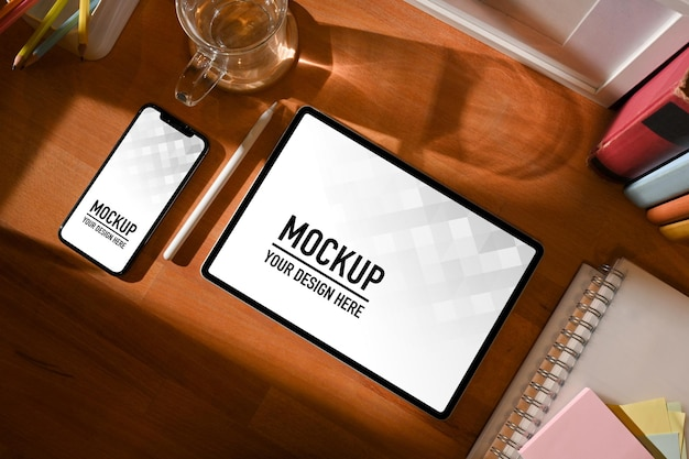 Vue de dessus de l'espace de travail avec tablette numérique et maquette de smartphone