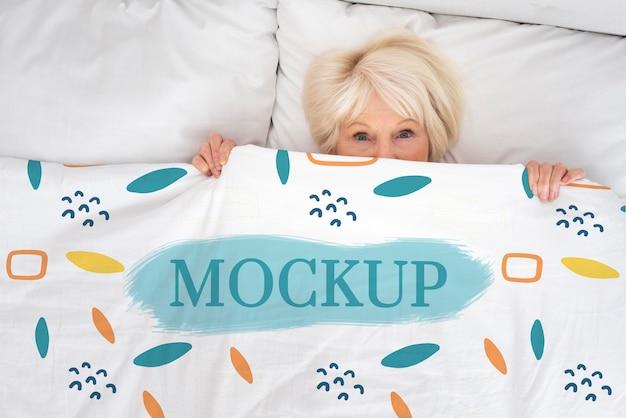 Vue de dessus femme pose dans son lit