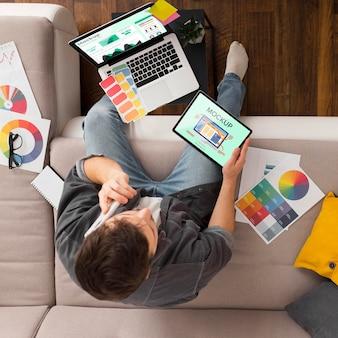Vue de dessus homme sur canapé avec tablette et maquette d'ordinateur portable