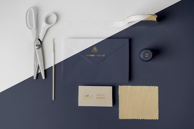 Vue de dessus de l'invitation de carnaval dans une enveloppe avec des ciseaux et du ruban adhésif