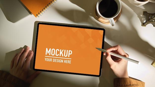 Vue de dessus de la main féminine à l'aide de maquette de tablette numérique sur table de travail blanche