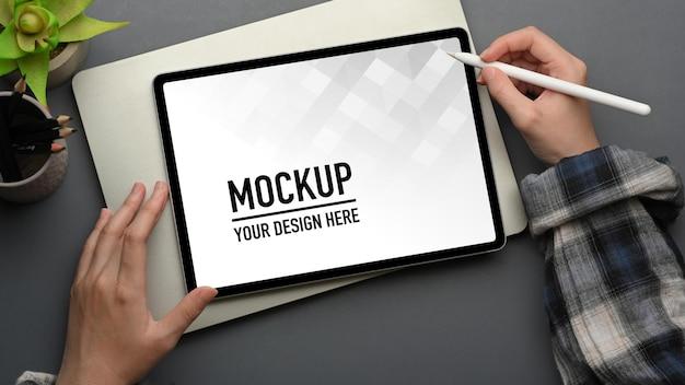 Vue de dessus de la main féminine avec un stylet travaillant sur une maquette de tablette numérique