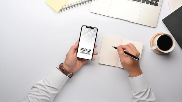 Vue de dessus de la main d'homme d'affaires travaillant avec une maquette de smartphone