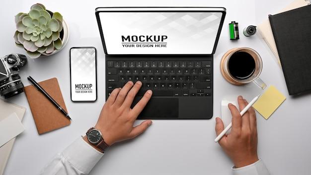 Vue de dessus de la main d'homme d'affaires travaillant avec tablette, maquette de smartphone et fournitures de bureau