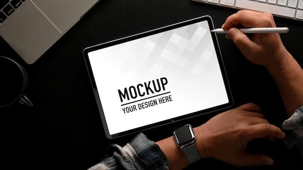 Vue de dessus de la main masculine à l'aide d'une maquette de tablette numérique