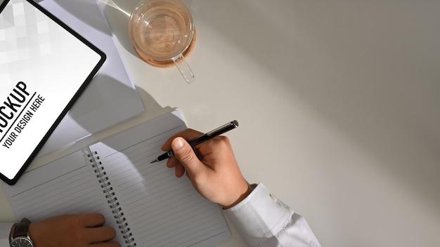 Vue de dessus de la main masculine écrit sur un cahier vierge tout en travaillant avec une maquette de tablette numérique