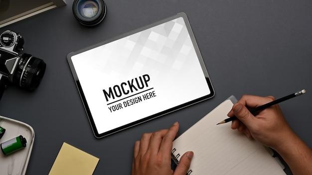 Vue de dessus de la main masculine écrit sur ordinateur portable sur l'espace de travail avec maquette de tablette