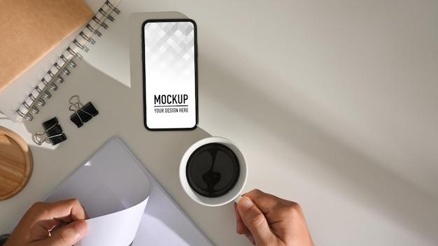 Vue de dessus de la main masculine tenant une tasse de café et de la paperasse avec maquette de smartphone