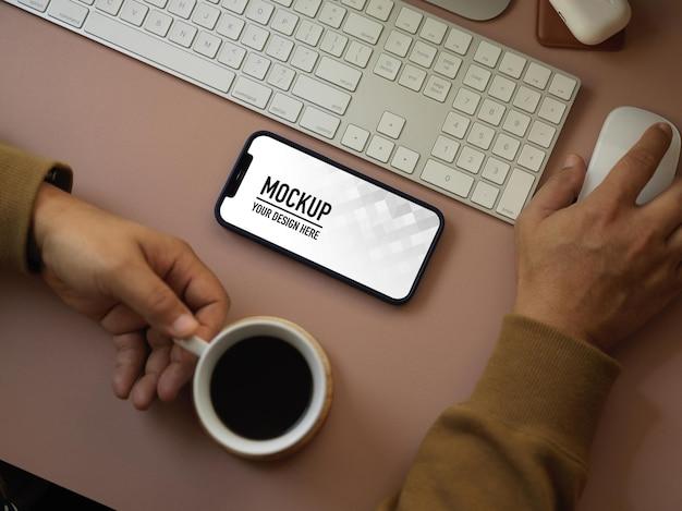 Vue de dessus de la main masculine travaillant avec un appareil informatique et une maquette de smartphone