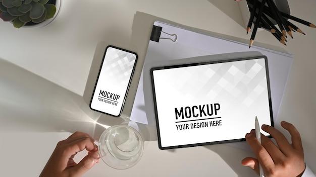 Vue de dessus de la main masculine travaillant avec une tablette numérique et une maquette de smartphone