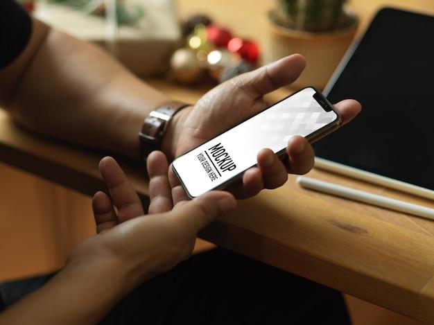 Vue de dessus de la main tenant la maquette du smartphone et les décorations de noël
