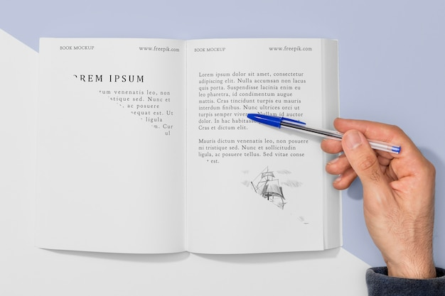 Vue de dessus main tenant un stylo sur une maquette de livre ouvert