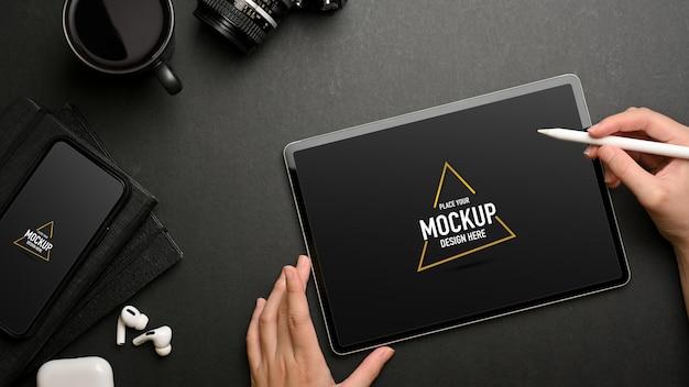 Vue de dessus des mains féminines à l'aide d'une maquette de tablette numérique sur un espace de travail créatif sombre