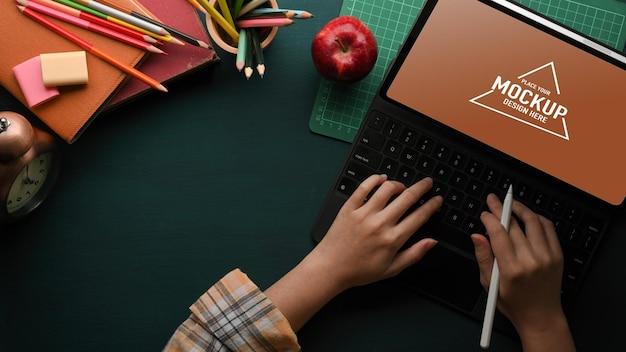 Vue de dessus des mains féminines tapant sur le clavier de la tablette