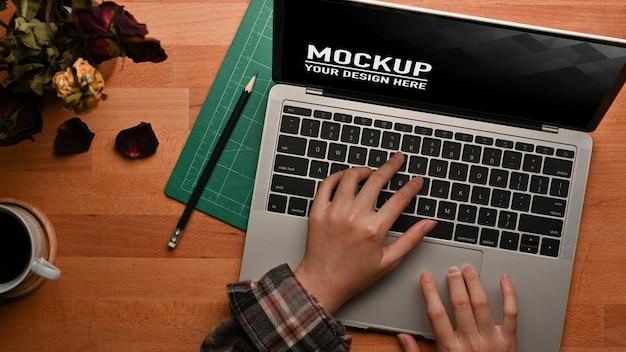 Vue de dessus des mains féminines tapant sur une maquette d'ordinateur portable sur une table en bois avec vase à fleur