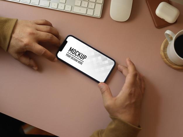 Vue de dessus des mains mâles à l'aide d'une maquette de smartphone horizontal