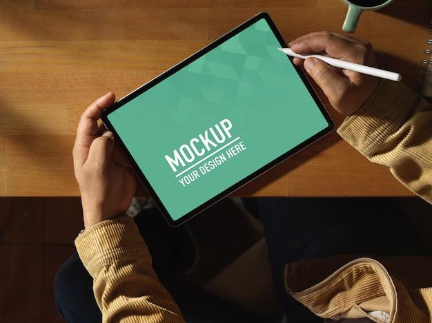 Vue de dessus des mains mâles à l'aide d'une maquette de tablette numérique