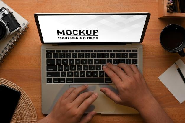 Vue de dessus des mains mâles tapant sur une maquette d'ordinateur portable