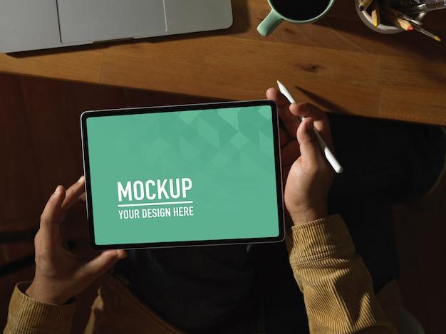 Vue de dessus des mains mâles tenant une maquette de tablette numérique