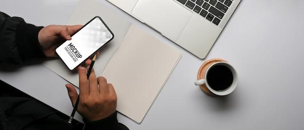 Vue de dessus des mains mâles travaillant avec une maquette de smartphone