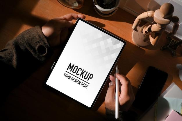Vue de dessus des mains mâles travaillant avec une maquette de tablette numérique