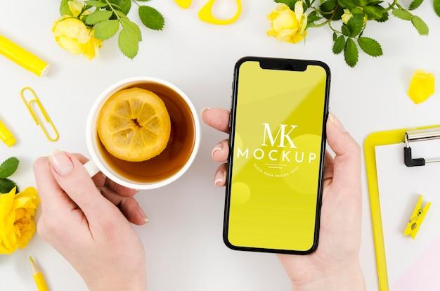 Vue de dessus mains tenant une maquette de smartphone avec du thé