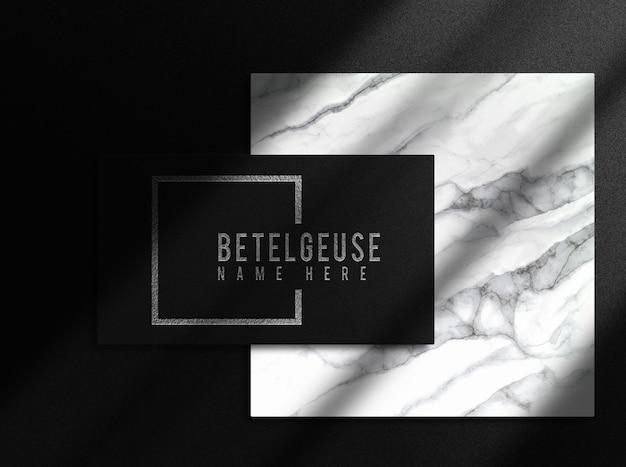 Vue de dessus de la maquette de carte de visite unique avec logo en relief argenté de luxe en gros plan avec podium en marbre