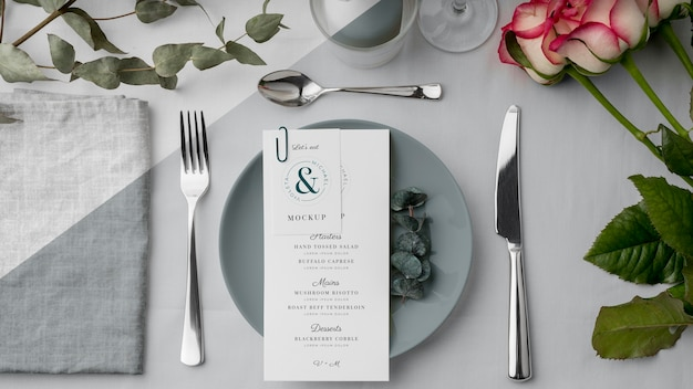 Vue de dessus de la maquette du menu de printemps sur une assiette avec des couverts et des fleurs